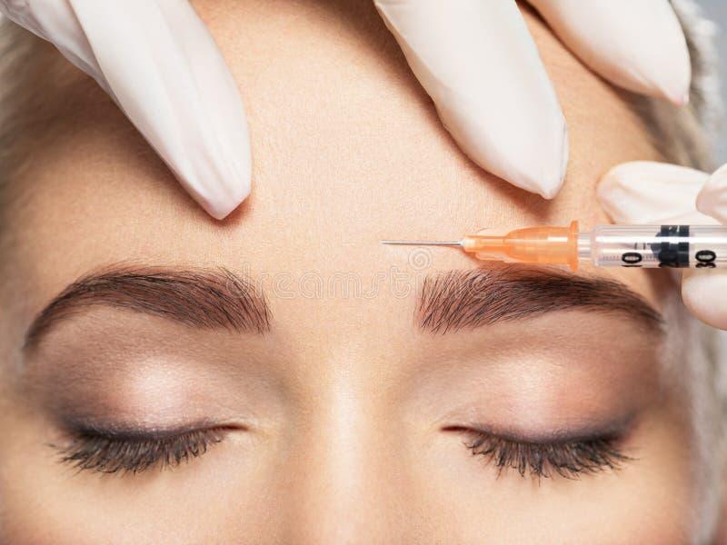 Femme obtenant l'injection cosmétique du botox près des yeux image stock