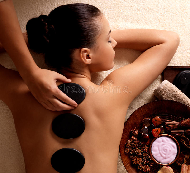 Femme obtenant le massage en pierre chaud dans le salon de station thermale.