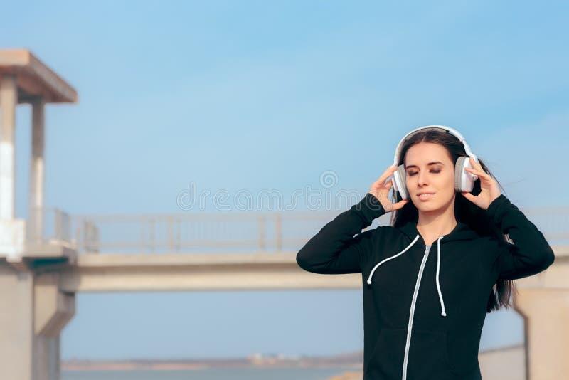 Femme occasionnelle écoutant la musique sur ses écouteurs et détente photos stock