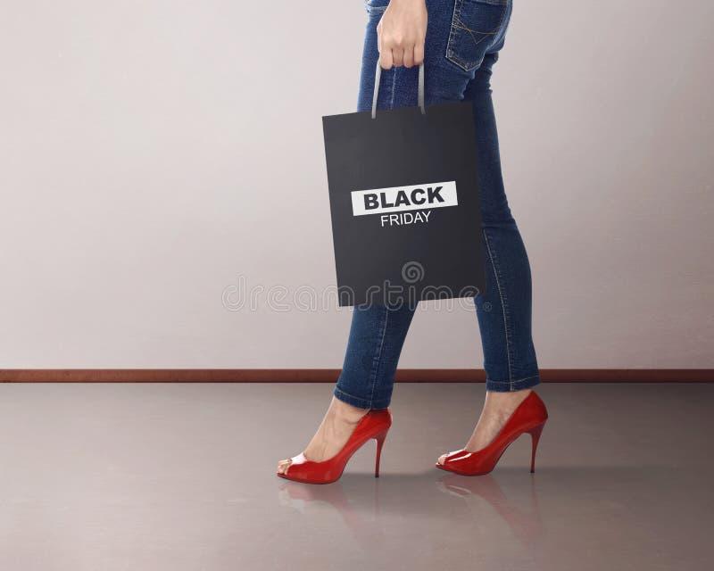 Femme occasionnelle avec le sac de papier de Black Friday images stock