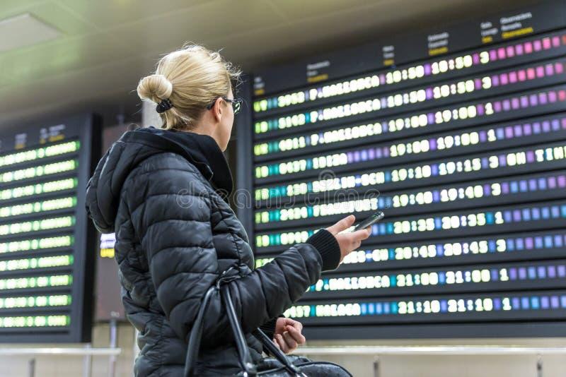 Femme occasionnelle dans l'aéroport international regardant le conseil de l'information de vol photos libres de droits