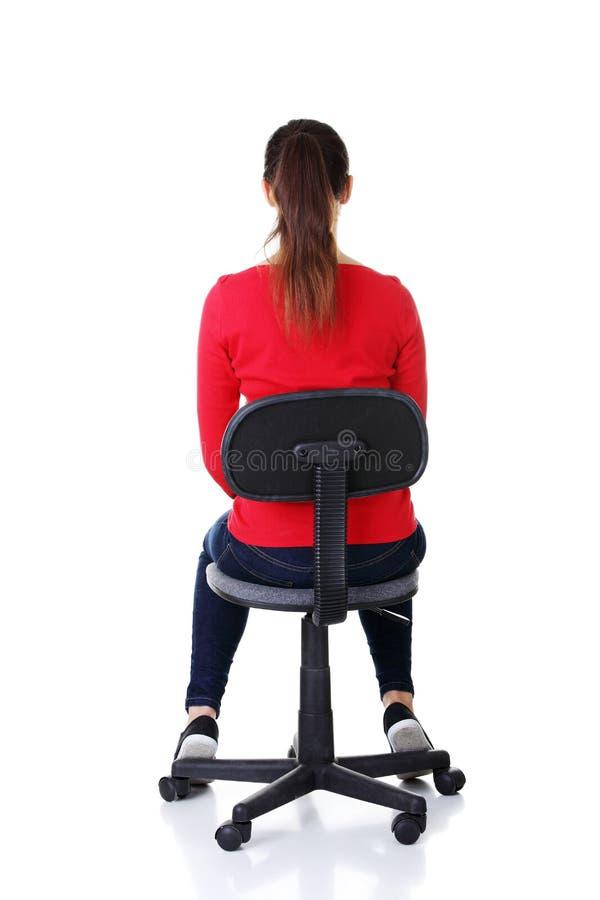 Femme occasionnelle heureuse s'asseyant sur une chaise. Vue arrière. image stock