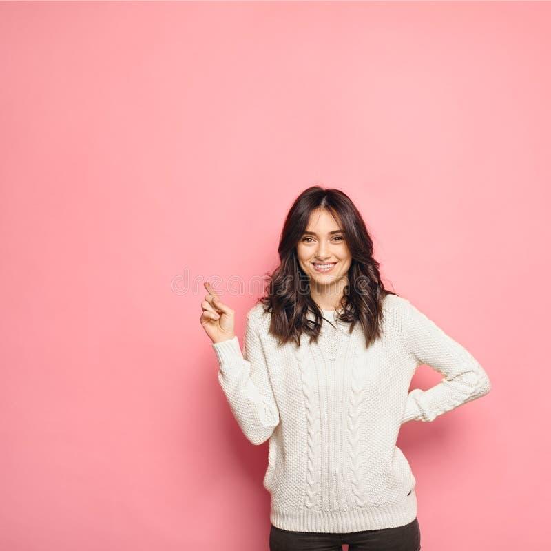 Femme occasionnelle utilisant un chandail confortable blanc indiquant le doigt la gauche photographie stock
