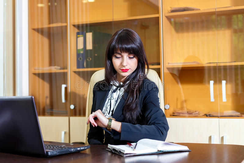 Femme occupée dans le bureau regardant sa montre image stock