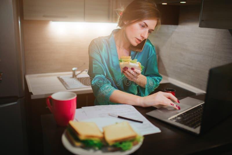 Femme occupée mangeant, café potable, parlant au téléphone, travaillant sur un ordinateur portable en même temps Faire de femme d photo stock