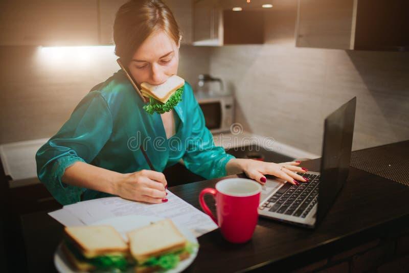 Femme occupée mangeant, café potable, parlant au téléphone, travaillant sur un ordinateur portable en même temps Faire de femme d photographie stock