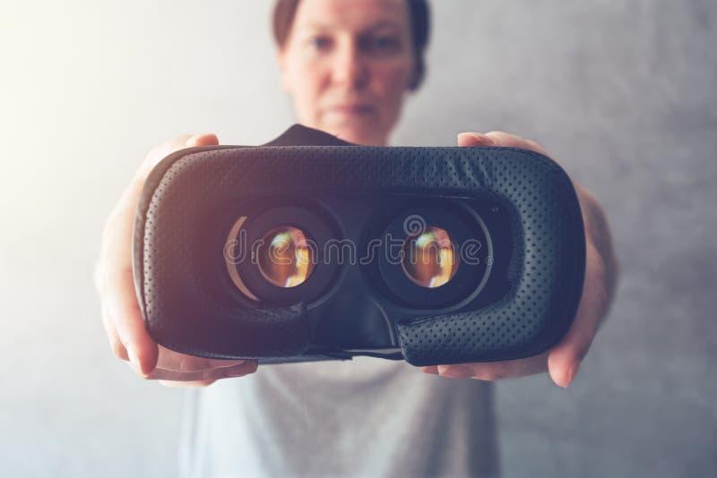 Femme offrant le casque de VR photographie stock