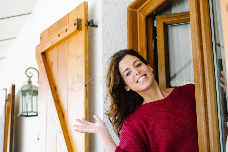 Femme ondulant de la fenêtre à la maison photo libre de droits