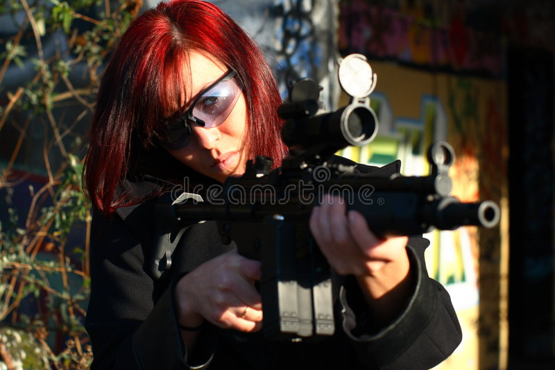 Femme orientant le canon d'assaut images stock