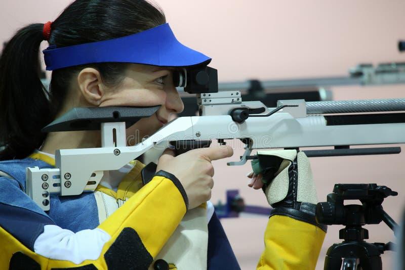 Femme orientant un fusil d'air pneumatique photographie stock libre de droits