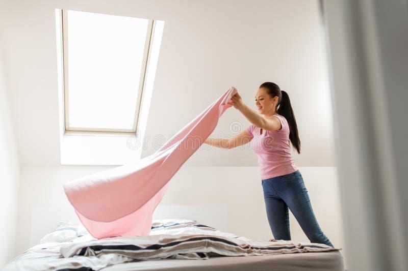 Femme ou femme au foyer heureuse faisant le lit à la maison images stock