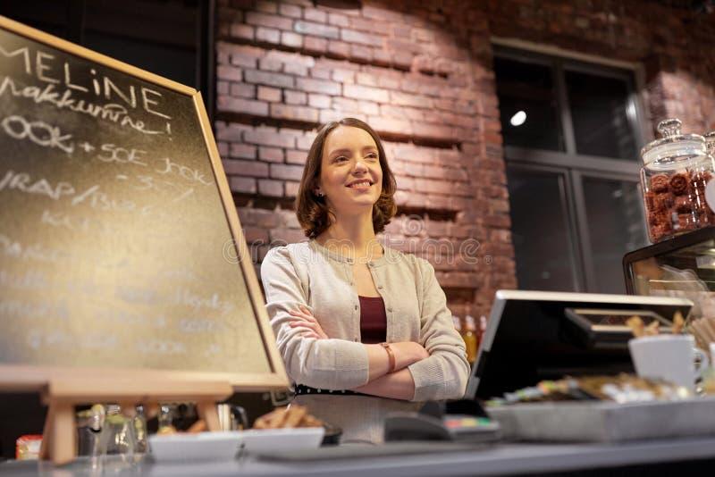 Femme ou barmaid heureuse au compteur de café image stock