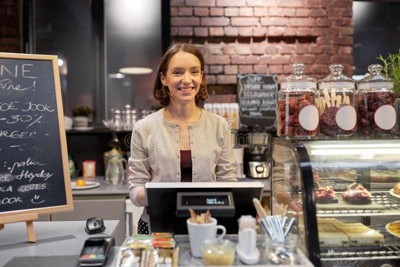 Femme ou barmaid heureuse avec la caisse au café photo libre de droits