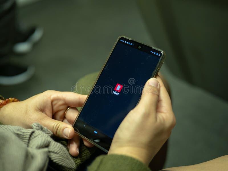 Femme ouvrant l'appli anonyme aveugle de forum de technologie avec le logo sur l'écran d'Android tout en permutant sur le métro photo stock