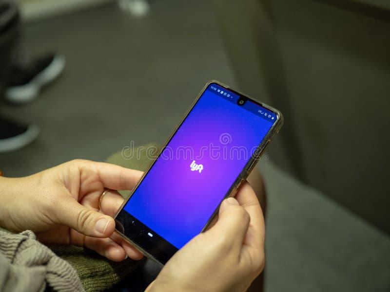 Femme ouvrant l'appli mobile de Lyft avec le logo sur l'écran d'Android tout en permutant sur le métro image libre de droits