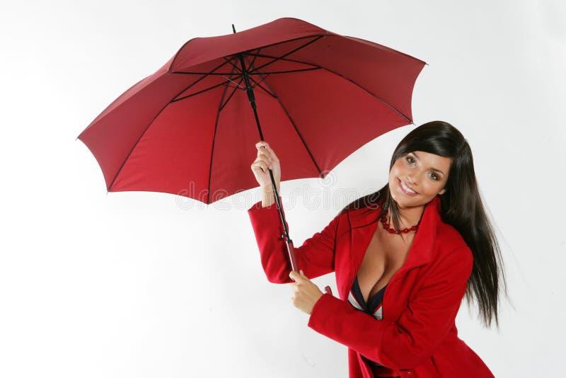 Femme ouvrant le parapluie rouge. image stock