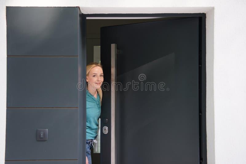 Femme ouvrant sa porte de maison photo libre de droits