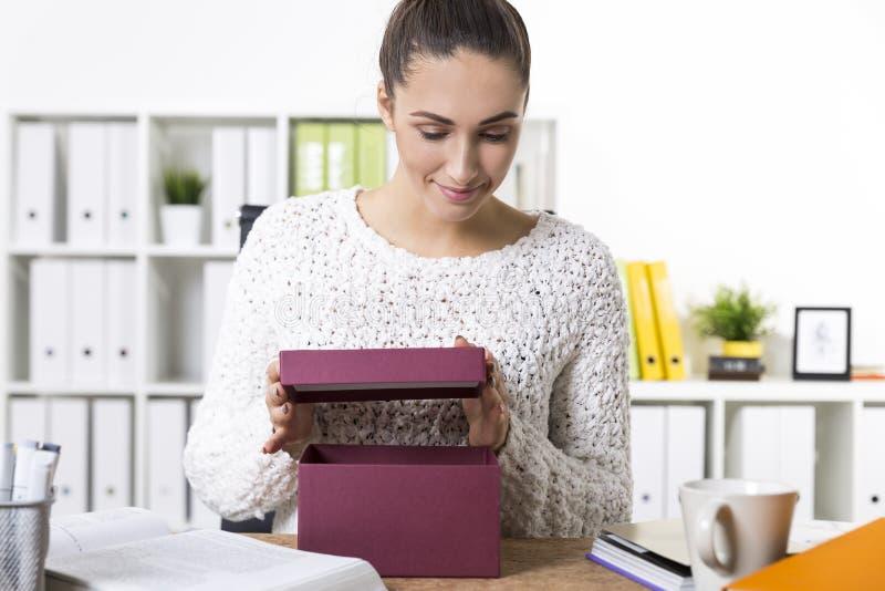 Femme ouvrant un présent dans une boîte rouge foncé au travail photo stock