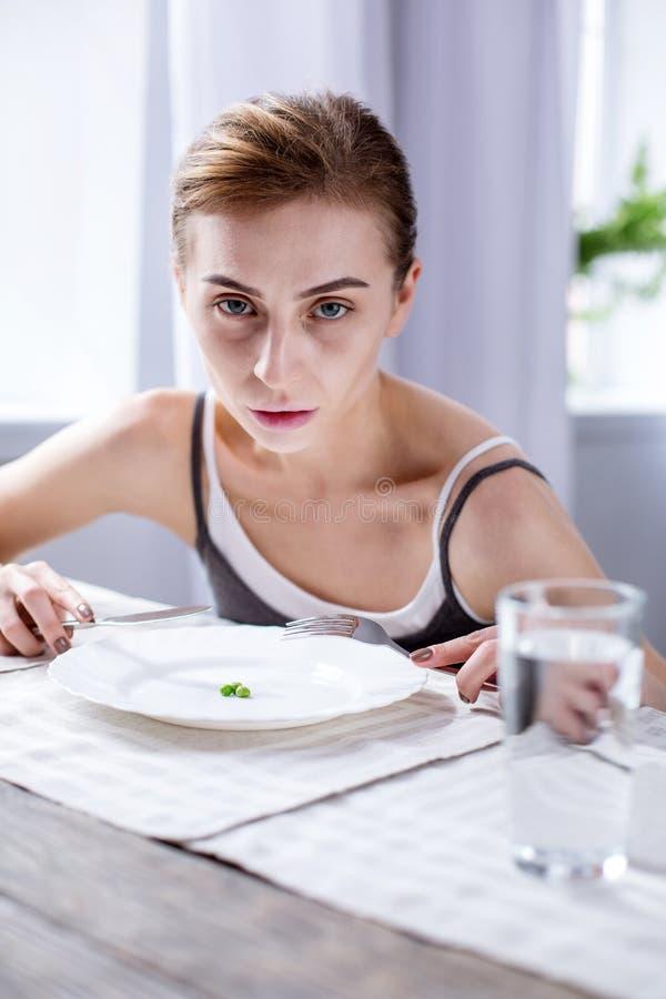 Femme pâle sombre s'asseyant à la table images stock