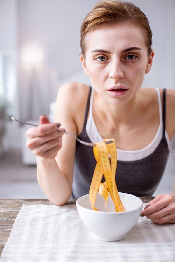 Femme pâle triste étant hantée avec son poids photos stock