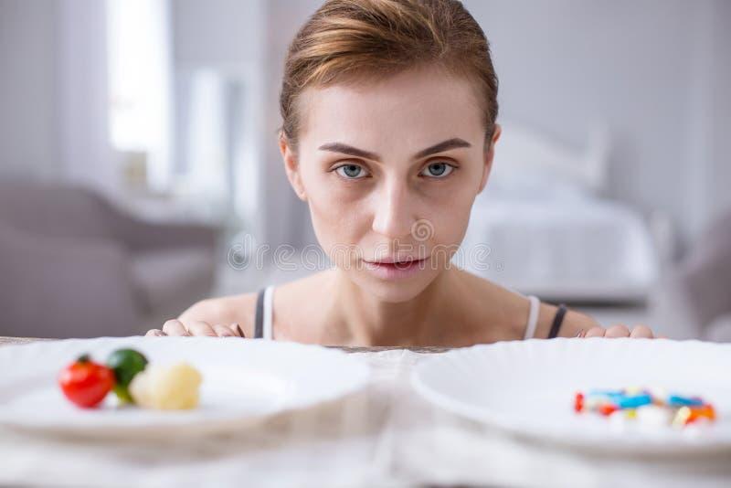 Femme pâle triste se tenant devant des plats photographie stock