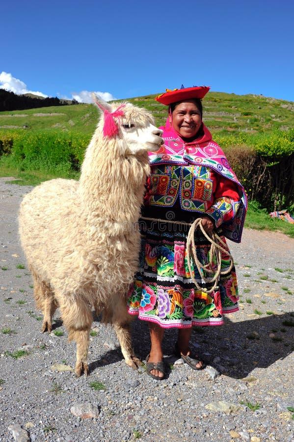 Femme péruvienne dans la robe traditionnelle avec le lama. images stock