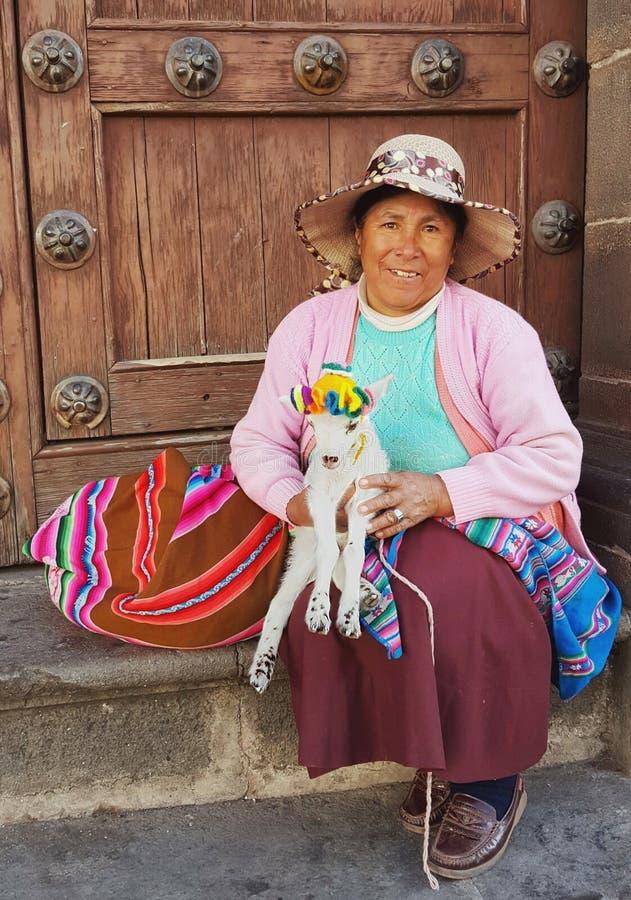 Femme péruvienne et son agneau chacun des deux dans le vêtement coloré, Cuzco Pérou image libre de droits