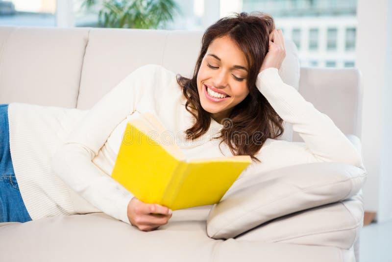 Femme paisible se trouvant sur le divan lisant un livre photo libre de droits