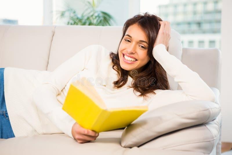 Femme paisible se trouvant sur le divan lisant un livre images libres de droits