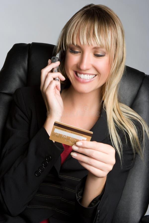 Femme par la carte de crédit de téléphone photo stock