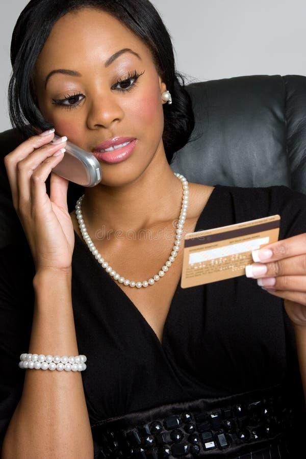 Femme par la carte de crédit de téléphone photo libre de droits