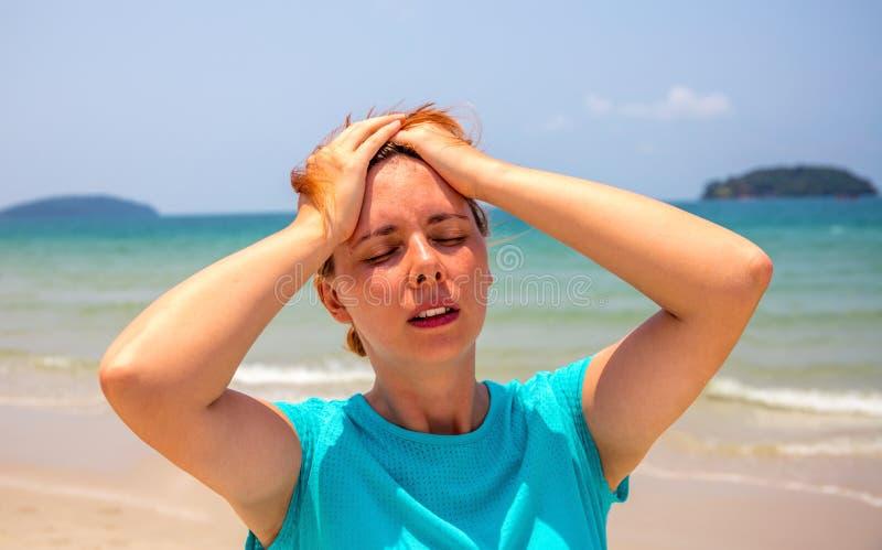 Femme par le bord de la mer avec l'insolation Problème de santé des vacances Médecine des vacances images stock