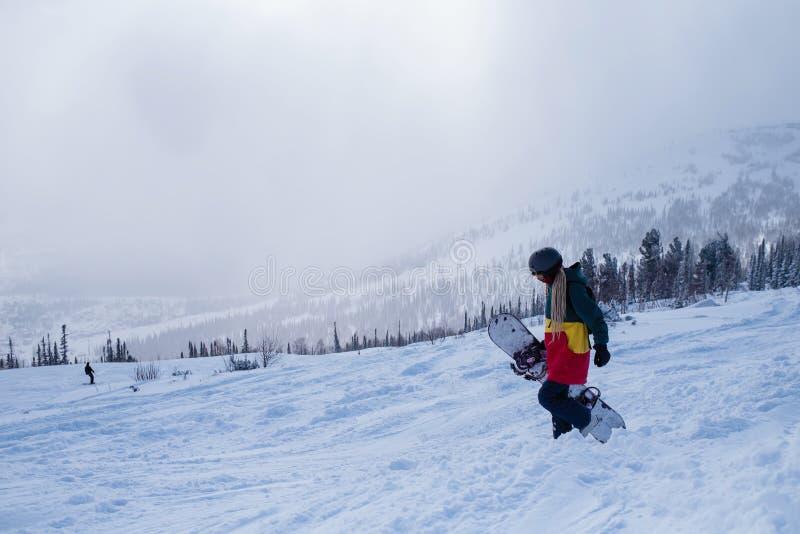 Femme parasitaire sur une pente neigeuse dans les montagnes sport images libres de droits