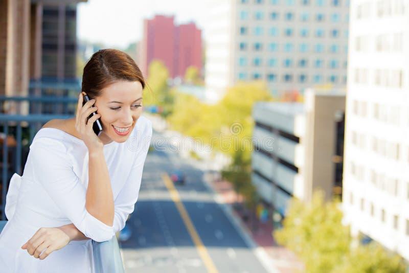 Femme parlant à un téléphone, balcon d'appartement photographie stock libre de droits