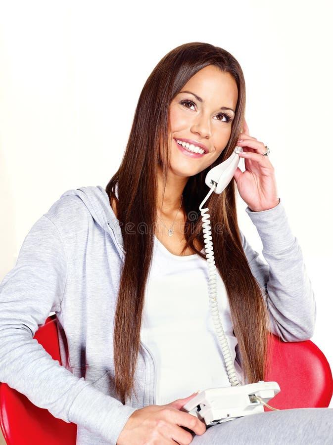 Femme parlant au-dessus du téléphone à la maison photo libre de droits