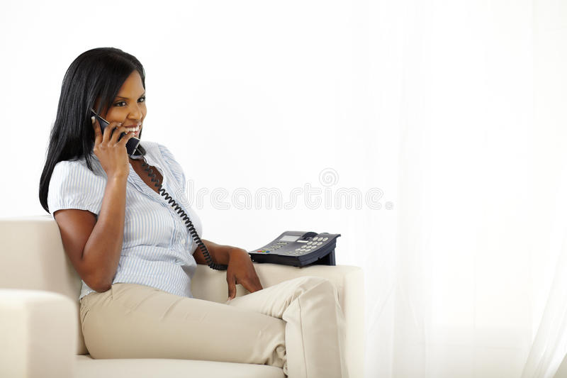 Femme parlant au téléphone à la maison photos stock