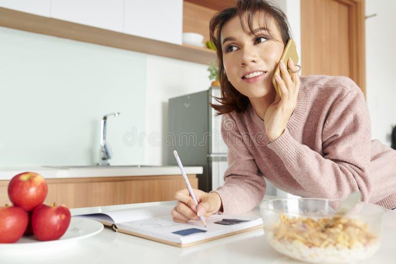 Femme parlant au téléphone pendant le petit déjeuner photographie stock