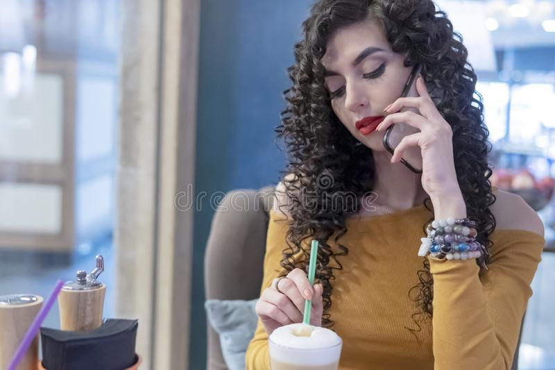 Femme parlant au téléphone remuant le café image libre de droits