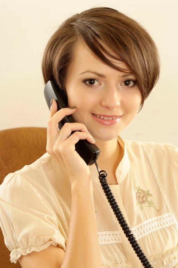 Femme parlant au téléphone sur un beige photo libre de droits