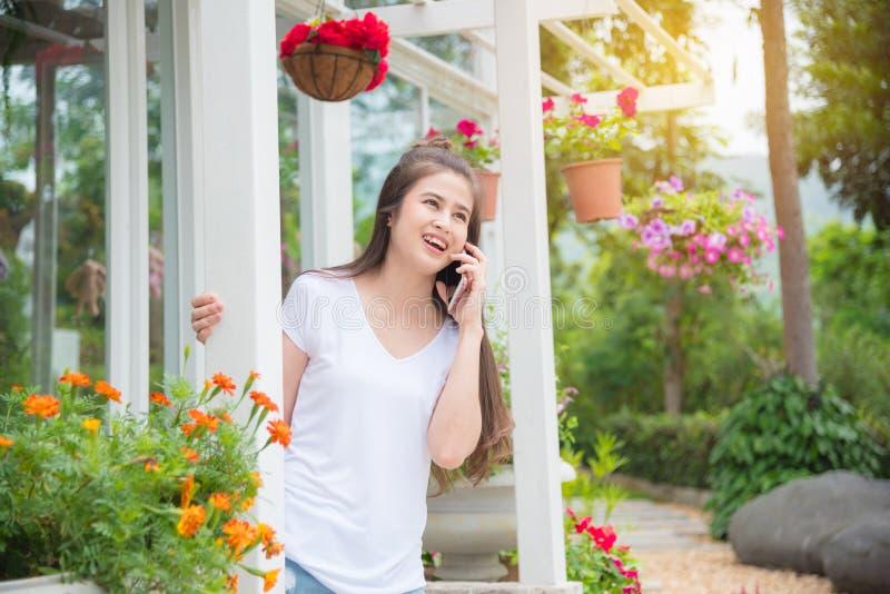 Femme parlant avec l'ami par l'intermédiaire du smartphone en parc image stock