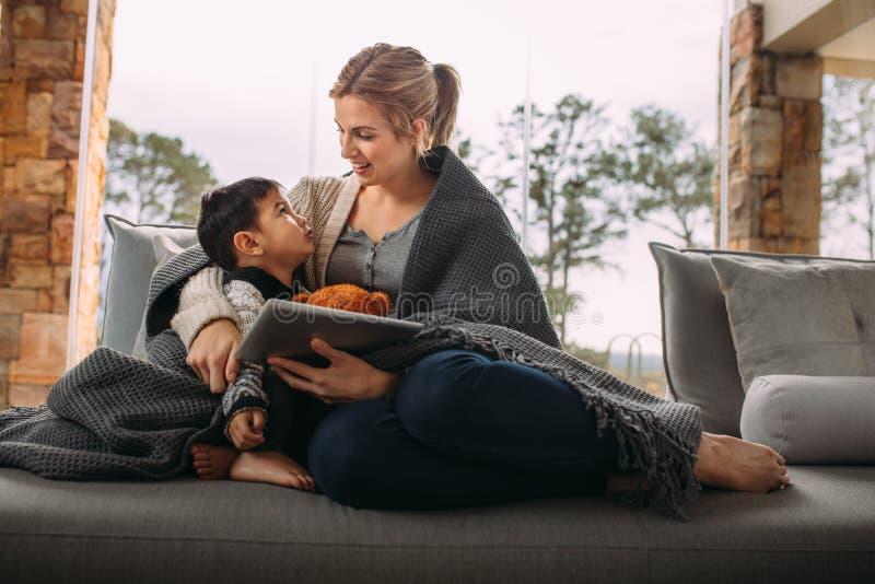 Femme parlant avec le fils s'asseyant à la maison images libres de droits
