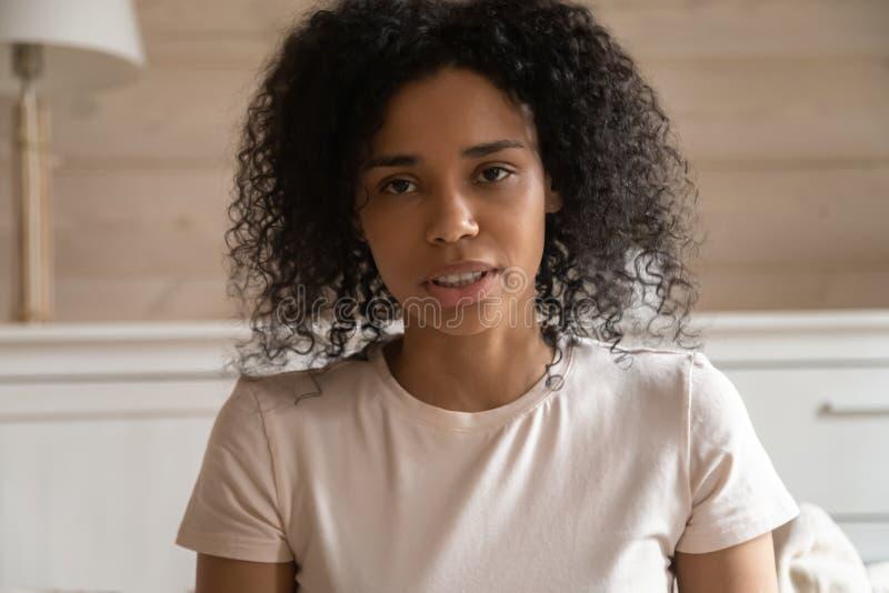 Femme parlante d'Africain de plan rapproché regardant la caméra faisant l'appel visuel images stock
