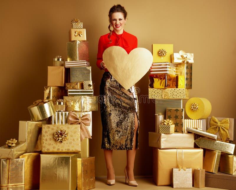Femme parmi 2 piles des cadeaux d'or montrant le coeur d'or photo libre de droits