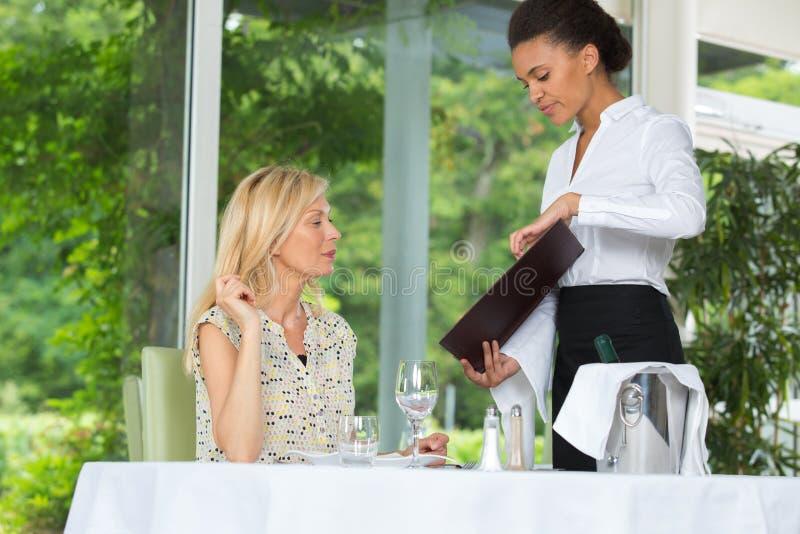 Femme passant commande à l'ordre d'écriture de serveuse de restaurant photographie stock libre de droits