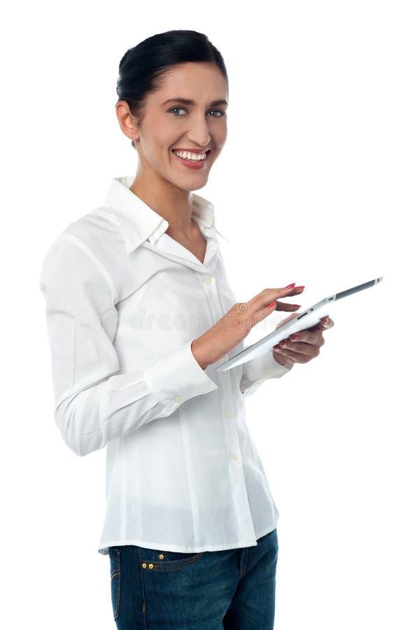Femme passant en revue sur le nouveau dispositif de pavé tactile image libre de droits