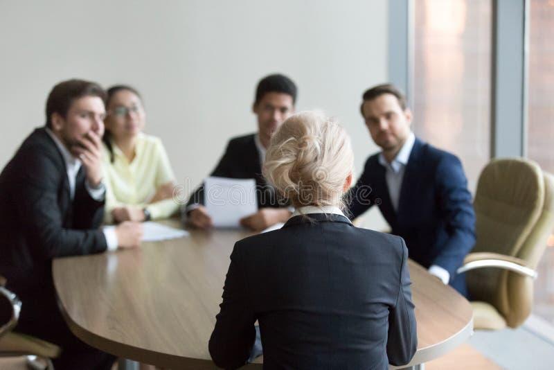 Femme passant l'entrevue d'emploi au bureau, interviewers sur le backgroun photos libres de droits