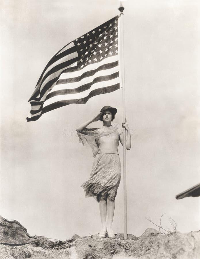 Femme patriote tenant le drapeau américain et la salutation images stock
