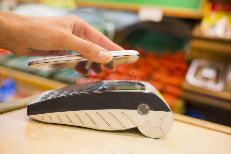 Femme payant avec la technologie de nfc au téléphone portable, achats, supe images stock