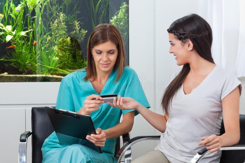 Femme payant par la carte de crédit au dentiste image libre de droits