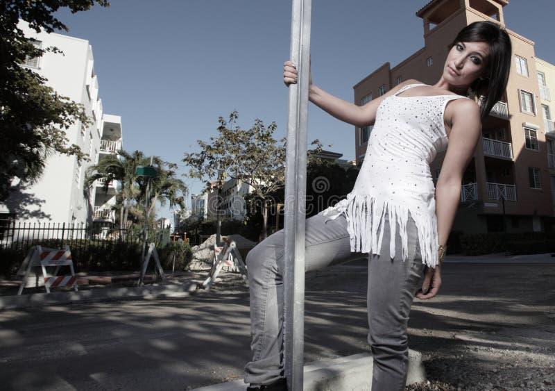 Femme pendant d'un pôle de rue photographie stock